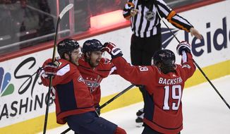 Washington Capitals defenseman Matt Niskanen, center, celebrates his goal with right wing Tom Wilson, left, and center Nicklas Backstrom (19), of Sweden, during the third period of an NHL hockey game against the New York Rangers, Friday, Dec. 8, 2017, in Washington. The Capitals won 4-2. (AP Photo/Nick Wass)