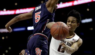 Arizona State guard Tra Holder, right, passes around St. John's guard Justin Simon during the first half of an NCAA college basketball game in Los Angeles, Friday, Dec. 8, 2017. (AP Photo/Chris Carlson)