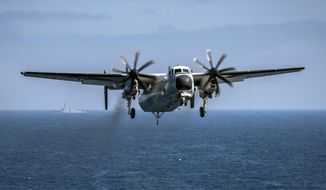 FILE - In this file image provided by the U.S. Navy, a C-2A Greyhound assigned to the Providers of Fleet Logistics Support Squadron (VRC) 30, prepares to land on the flight deck aboard the aircraft carrier USS Theodore Roosevelt (CVN 71) on Aug. 22, 2017. The U.S. Navy says it will deploy deep water salvage experts to search for a similar C-2A Greyhound transport aircraft that crashed in the western Pacific last month, killing three sailors. (Mass Communication Specialist 3rd Class Alex Corona/U.S. Navy via AP, File)