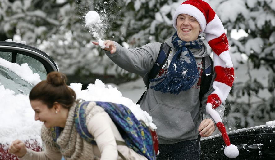 A Belhaven University student throws a snowball at a school mate as students blow off some final exam anxiety with a series of campus wide snowball fights Friday, Dec. 8, 2017, in Jackson, Miss. The forecast called for a wintry mix of rain and snow across several states in the south. (AP Photo/Rogelio V. Solis)