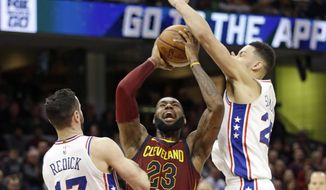 Cleveland Cavaliers' LeBron James, center, shoots between Philadelphia 76ers' JJ Redick, left and Ben Simmons during the second half of an NBA basketball game Saturday, Dec. 9, 2017, in Cleveland. The Cavaliers won 105-98. (AP Photo/Tony Dejak)