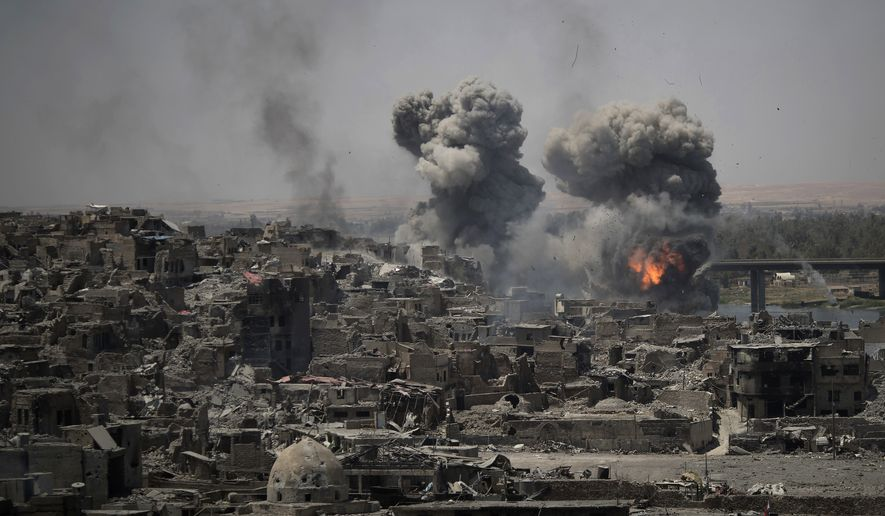 In this July 11, 2017, file photo, airstrikes target Islamic State positions on the edge of the Old City in Mosul, Iraq. Iraq said Saturday, Dec. 9, 2017, that its war on the Islamic State is over after more than three years of combat operations drove the extremists from all of the territory they once held. Prime Minister Haider al-Abadi announced Iraqi forces were in full control of the country's border with Syria. (AP Photo/Felipe Dana, File)