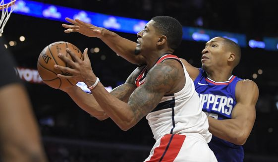 Washington Wizards guard Bradley Beal, left, shoots as Los Angeles Clippers forward Wesley Johnson defends during the second half of an NBA basketball game, Saturday, Dec. 9, 2017, in Los Angeles. The Clippers won 113-112. (AP Photo/Mark J. Terrill)