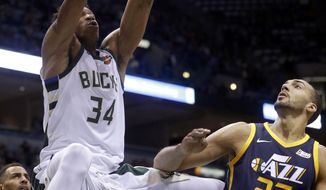 Milwaukee Bucks' Giannis Antetokounmpo dunks over Utah Jazz's Rudy Gobert during the first half of an NBA basketball game Saturday, Dec. 9, 2017, in Milwaukee. (AP Photo/Aaron Gash)
