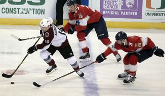 Colorado Avalanche's Sven Andrighetto (10), of Switzerland, moves the puck on Florida Panthers' Nick Bjugstad (27) and Keith Yandle (3) during the second period of an NHL hockey game, Saturday, Dec. 9, 2017, in Sunrise, Fla. (AP Photo/Luis M. Alvarez)