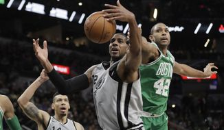 San Antonio Spurs forward LaMarcus Aldridge (12) and Boston Celtics forward Al Horford (42) reach for a rebound during the first half of an NBA basketball game Friday, Dec. 8, 2017, in San Antonio. (AP Photo/Eric Gay)