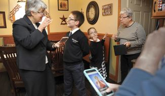 This photo taken Nov. 20, 2017, shows Sister Kathleen Schipani, left, director of the office for persons with disabilities and the deaf apostolate in the Archdiocese of Philadelphia, signs/talks with Robert Pomroy, second from left, 11, while his sister, Rachael Pomroy, second from right, 8, signs/talks with their grandmother, Pat Pomroy, right, after school at their Cryodon home. The siblings are deaf. Schipani found many existing apps for learning American Sign Language, but there were none dedicated to religious terms, daily devotions or prayers. So she created one, an app called Religious Signs for Families. (Tom Gralish/The Philadelphia Inquirer via AP)