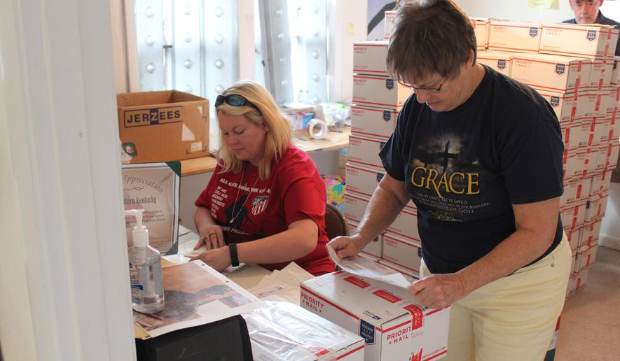 Tara Bohannon, left, of the Hugs Project of Western Kentucky prepares mailing labels while Cindylou Ziegler, right, affixes them to some of the 500 Christmas packages being sent by the organization to service members overseas. The Hugs Project sends packages to overseas military men and women throughout the year. (David B. Snow /The Paducah Sun via AP)