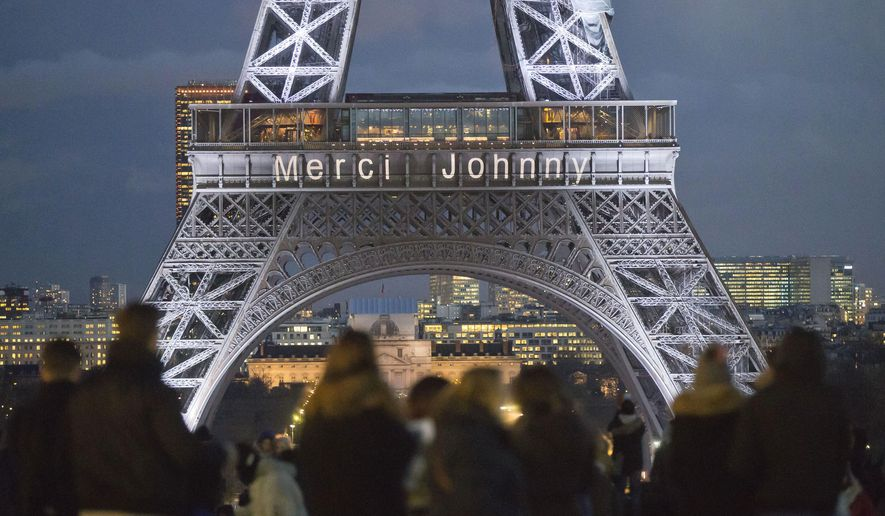 """The words """"Thank you Johnny"""" is displayed on the Eiffel Tower referring to late French rock star Johnny Hallyday in Paris, France, Friday, Dec. 8, 2017. French President Emmanuel Macron and hundreds of thousands of fans are expected to pay tribute to the late French rock star Johnny Hallyday on Saturday as his funeral procession weaves through Paris. (AP Photo/Michel Euler)"""