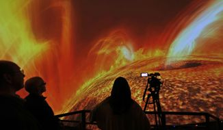 In this Wednesday, Dec. 6, 2017 photo, people watch interstellar bodies move through space during a media preview at the planetarium at Liberty Science Center in Jersey City, N.J. The  newly refurbished planetarium is the largest in the western hemisphere and uses ten advanced projectors to produce an 8K resolution. It opens to the public on Saturday, Dec. 9, 2017. (AP Photo/Seth Wenig)