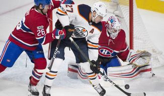 Edmonton Oilers' Milan Lucic (27) moves in on Montreal Canadiens goaltender Antti Niemi as Canadiens' Jeff Petry defends during the third period of an NHL hockey game Saturday, Dec. 9, 2017, in Montreal. (Graham Hughes/The Canadian Press via AP)