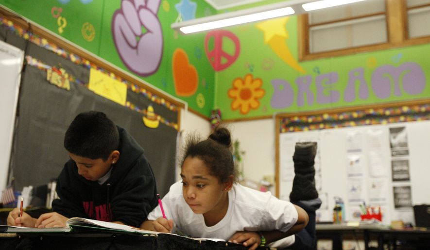 In a Dec. 1, 2017 photo, fourth-graders Mia Marrero, center, and Alonzo Gonzales work in Diane Brown's class at Washington Elementary in Billings, Mont.   Changes at the school were sparked by the adoption of methods espoused by the Ron Clark Academy, a private school in Georgia. The methods are taking root around School District 2. (Casey Page/The Billings Gazette via AP)