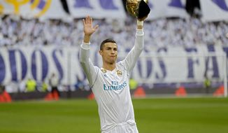 Real Madrid's Cristiano Ronaldo holds up one of his five Golden Ball trophy prior the Spanish La Liga soccer match between Real Madrid and Sevilla at the Santiago Bernabeu stadium in Madrid, Saturday, Dec. 9, 2017. (AP Photo/Francisco Seco)