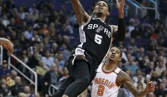 San Antonio Spurs guard Dejounte Murray (5) drives to the basket past Phoenix Suns' Tyler Ulis during the first half of an NBA basketball game Saturday, Dec. 9, 2017, in Phoenix. (AP Photo/Ralph Freso)