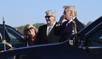 President Donald Trump, right, standing with Mississippi Gov. Phil Bryant, center, blows a kiss to the crowd after arriving on Air Force One at Jackson-Medgar Wiley Evers International Airport in Jackson, Miss., Saturday, Dec. 9, 2017. Trump is speaking at the opening of the Mississippi Civil Rights Museum in Jackson. (AP Photo/Susan Walsh)