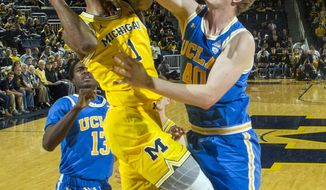 Michigan guard Charles Matthews (1) has his shot attempt blocked by UCLA center Thomas Welsh (40) in the first half of an NCAA college basketball game at Crisler Center in Ann Arbor, Mich., Saturday, Dec. 9, 2017. (AP Photo/Tony Ding)