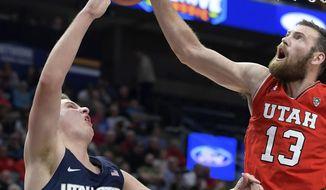 Utah forward David Collette (13) blocks the shot of Utah State guard Sam Merrill (3) during an NCAA college basketball game Saturday, Dec. 9, 2017, in Salt Lake City, Utah. (Eli Lucero/Herald Journal via AP)