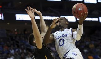 Seton Hall's Khadeen Carrington, right, takes a shot past Virginia Commonwealth's Sean Mobley, left,  during the first half of an NCAA college basketball game Saturday, Dec. 9, 2017, in Newark, N.J. (AP Photo/Mel Evans)