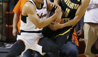 Oklahoma State guard Kendall Smith, left, and Wichita State guard Landry Shamet (11) fight for the ball in the first half of an NCAA college basketball game in Stillwater, Okla., Saturday, Dec. 9, 2017. (AP Photo/Sue Ogrocki)