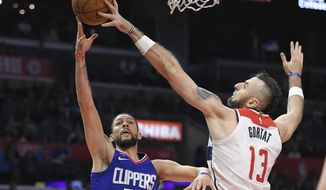 Los Angeles Clippers guard Austin Rivers, left, shoots as Washington Wizards center Marcin Gortat, of Serbia, blocks his shot during the first half of an NBA basketball game, Saturday, Dec. 9, 2017, in Los Angeles. (AP Photo/Mark J. Terrill)