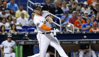 FILE - In this June 23, 2017, file photo, Miami Marlins' Giancarlo Stanton hits a home run in the third inning of a baseball game against the Chicago Cubs in Miami.  A person familiar with the negotiations says the New York Yankees and Miami Marlins are working on a trade that would send slugger Giancarlo Stanton to New York and infielder Starlin Castro to Miami.  The person spoke to The Associated Press on condition of anonymity Saturday, Dec. 9, 2017, because no agreement has been completed. (AP Photo/Wilfredo Lee, File) **FILE**
