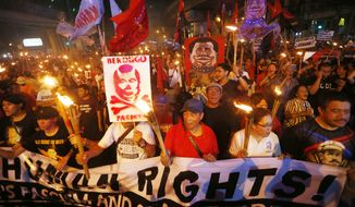 Protesters carry torches as they march toward the Presidential Palace in Manila to mark the United Nations Declaration of International Human Rights Day Sunday, Dec. 10, 2017 in Manila, Philippines. Thousands of protesters accused President Duterte of human rights violations in his more than a year in office and are demanding his ouster. (AP Photo/Bullit Marquez)