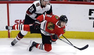 Chicago Blackhawks defenseman Jordan Oesterle, front, is checked by Arizona Coyotes center Dylan Strome during the first period of an NHL hockey game Sunday, Dec. 10, 2017, in Chicago. (AP Photo/Nam Y. Huh)