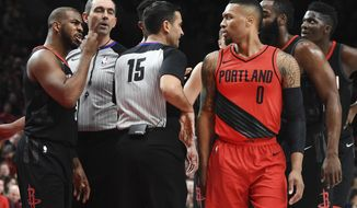 Houston Rockets guard Chris Paul, left, exchanges words with Portland Trail Blazers guard Damian Lillard after being called for a foul when he knocked Lillard down during the first half of an NBA basketball game in Portland, Ore., Saturday, Dec. 9, 2017. (AP Photo/Steve Dykes)