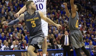 Kansas guard Sviatoslav Mykhailiuk (10) tips the ball to a teammate while covered by Arizona State forward Mickey Mitchell (3) and guard Tra Holder (0) during the first half of an NCAA college basketball game in Lawrence, Kan., Sunday, Dec. 10, 2017. (AP Photo/Orlin Wagner)