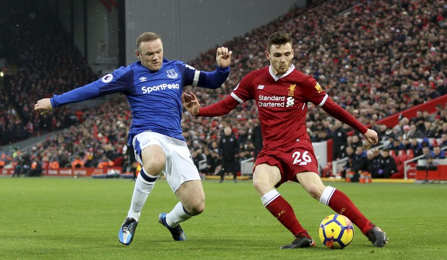 Everton's Wayne Rooney, left, and Liverpool's Andrew Robertson battle for the ball during their English Premier League soccer match at Anfield, Liverpool, England, Sunday, Dec. 10, 2017. (Peter Byrne/PA via AP)