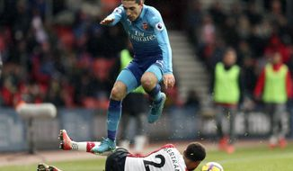 Arsenal's Hector Bellerin, top, jumps over Southampton's Ryan Bertrand as they battle for the ball during the English Premier League soccer match at St Mary's Stadium, Southampton, England, Sunday Dec. 10, 2017. (Adam Davy/PA via AP)