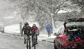 People brave the cold as snow continues to fall near Castleton, England,  Saturday Doc. 9, 2017, as widespread disruption is expected across large parts of the UK.  Forecasters are warning that some communities could be cut off as temperatures plummet and heavy snow settles on the region. (John Giles/PA via AP)