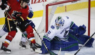 Vancouver Canucks goalie Anders Nilsson, right, from Sweden, stops Calgary Flames' Matthew Tkachuk from scoring during first-period NHL hockey game action in Calgary, Saturday, Dec. 9, 2017. (Jeff McIntosh/The Canadian Press via AP)
