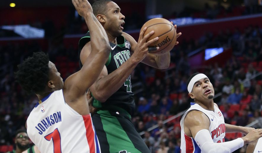 Boston Celtics forward Al Horford, center, goes to the basket against Detroit Pistons forwards Stanley Johnson (7) and Tobias Harris, right, during the first half of an NBA basketball game Sunday, Dec. 10, 2017, in Detroit. (AP Photo/Duane Burleson)
