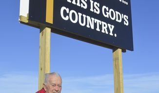 ADVANCE FOR USE SUNDAY, DEC. 10 - In this Nov. 27, 2017 photo, former state Sen. Richard Peterson poses by a religious sign in Norfolk, Neb. Peterson is paying to create and erect several small billboards that remind drivers around Norfolk that God is always available to listen. ( Jerry Guenther/The Norfolk Daily News via AP)