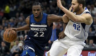 Minnesota Timberwolves forward Andrew Wiggins (22) drives against Dallas Mavericks forward Maximilian Kleber (42), of Germany, during the first quarter of an NBA basketball game on Sunday, Dec. 10, 2017, in Minneapolis. Wiggins was called for an offensive foul. (AP Photo/Hannah Foslien)