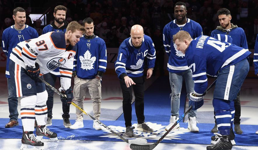 Toronto FC coach Greg Vanney, rear left to right, and players Drew Moor, Sebastian Giovinco, Michael Bradley, Jozy Altidore and Jonathan Osorio take part in a ceremonial puck drop with Edmonton Oilers centre Connor McDavid (97) and Toronto Maple Leafs centre Leo Komarov (47) ahead of first period NHL hockey action in Toronto on Sunday, Dec. 10, 2017. (Frank Gunn/The Canadian Press via AP)