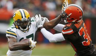 Green Bay Packers wide receiver Davante Adams (17) holds off Cleveland Browns defensive back Jason McCourty (30) in the second half of an NFL football game, Sunday, Dec. 10, 2017, in Cleveland. (AP Photo/Ron Schwane)