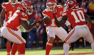 Kansas City Chiefs running back Kareem Hunt (27) celebrates his touchdown against the Oakland Raiders with teammates wide receiver Tyreek Hill (10) and wide receiver Albert Wilson (12) during the first half of an NFL football game in Kansas City, Mo., Sunday, Dec. 10, 2017. (AP Photo/Charlie Riedel)