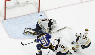 St. Louis Blues' Vladimir Tarasenko (91), of Russia, scores the winning goal past Buffalo Sabres goalie Robin Lehner, of Sweden, as Sabres' Evander Kane (9) and Jack Eichel (15) defend during overtime of an NHL hockey game Sunday, Dec. 10, 2017, in St. Louis. (AP Photo/Jeff Roberson)
