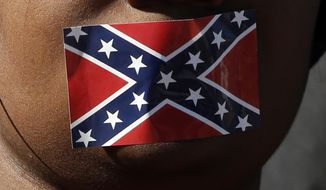 In this file photo, Brittany Brent of Jackson, wears a Confederate battle flag sticker on her mouth as part of a silent protest to the current Mississippi state flag, on which it rests prominently, during the grand opening ceremony for the two museums, the Museum of Mississippi History and the Mississippi Civil Rights Museum, Saturday, Dec. 9, 2017, in Jackson, Miss. A small group of protestors wore the stickers and stood silently holding an alternative flag during the program. (AP Photo/Rogelio V. Solis)