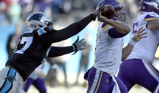 Minnesota Vikings' Case Keenum, right, tries to throw a pass as Carolina Panthers' Mario Addison, left, reaches in during the second half of an NFL football game in Charlotte, N.C., Sunday, Dec. 10, 2017. (AP Photo/Mike McCarn)