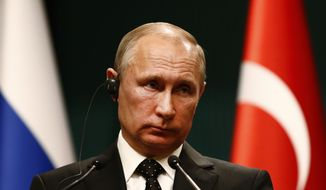Russia's President Vladimir Putin, listens during a joint news statement with Turkey's President Recep Tayyip Erdogan, following their meeting at the Presidential Palace in Ankara, Monday, Dec. 11, 2017. The two men met Monday evening to discuss developments in Syria and the Middle East, as well as bilateral relations, according to the Turkish President's office. (AP Photo/Burhan Ozbilici)