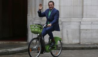 Arnold Schwarzenegger arrives on bicycle to meet Paris mayor Anne Hdalgo, Monday Dec. 11, 2017 in Paris. Schwarzenegger is in Paris to attend the One Planet climate summit Tuesday with more than 50 world leaders and co-hosted by the U.N. and the World Bank. (AP Photo/Thibault Camus)