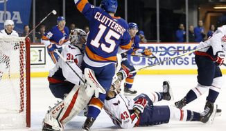 New York Islanders right wing Cal Clutterbuck (15) collides with Washington Capitals goalie Philipp Grubauer (31), of Germany, as Capitals right wing Tom Wilson (43) slides into Grubauer during the second period of an NHL hockey game in New York, Monday, Dec. 11, 2017. (AP Photo/Kathy Willens)