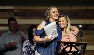 "ADVANCE FOR USE TUESDAY, DEC. 12, 2017 AND THEREAFTER-Kim Silvers, left, hugs her daughter, Emily, while speaking during a graduation ceremony from the Appalachian Judicial Circuit family drug court program in Ellijay, Ga., Tuesday, April 11, 2017. ""I went into this program and I was kid-less, jobless, broken, I didn't have anything,"" said Silvers, her eyes moist. ""It was the hardest thing I've ever had to do. But it is the most rewarding."" Without it, she said as her daughters stood behind her, ""I would be dead right now."" (AP Photo/David Goldman)"