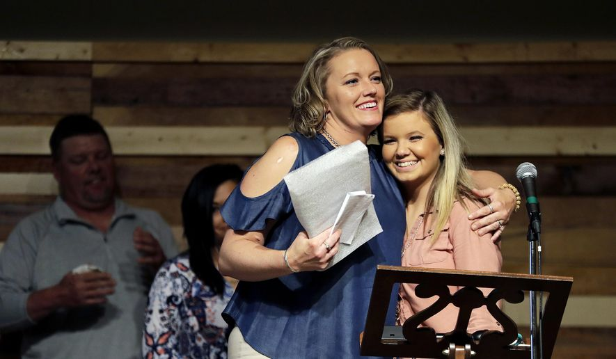 """ADVANCE FOR USE TUESDAY, DEC. 12, 2017 AND THEREAFTER-Kim Silvers, left, hugs her daughter, Emily, while speaking during a graduation ceremony from the Appalachian Judicial Circuit family drug court program in Ellijay, Ga., Tuesday, April 11, 2017. """"I went into this program and I was kid-less, jobless, broken, I didn't have anything,"""" said Silvers, her eyes moist. """"It was the hardest thing I've ever had to do. But it is the most rewarding."""" Without it, she said as her daughters stood behind her, """"I would be dead right now."""" (AP Photo/David Goldman)"""