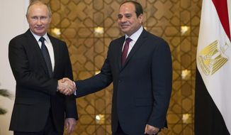 Russian President Vladimir Putin, left, and Egyptian President Abdel-Fattah El-Sissi, shake hands during their meeting in Cairo, Egypt, Monday, Dec. 11, 2017. (AP Photo/Alexander Zemlianichenko/ pool photo via AP)