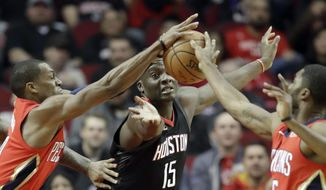 Houston Rockets' Clint Capela (15) reaches for a rebound with New Orleans Pelicans' Rajon Rondo, left, and E'Twaun Moore, right, during the first quarter of an NBA basketball game Monday, Dec. 11, 2017, in Houston. (AP Photo/David J. Phillip)