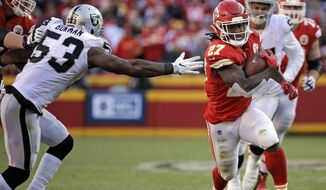 Kansas City Chiefs running back Kareem Hunt (27) carries the ball away from Oakland Raiders linebacker NaVorro Bowman (53) during the second half of an NFL football game in Kansas City, Mo., Sunday, Dec. 10, 2017. (AP Photo/Charlie Riedel)